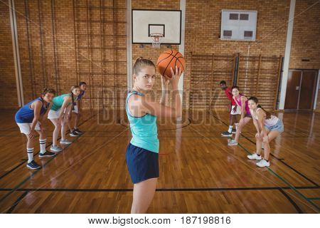 Portrait of high school girl about to take a penalty shot while playing basketball in the court