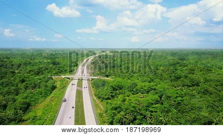 Aerial view of vehicles driving on the expressway while winding through forested areas