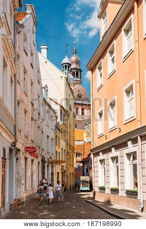 Riga, Latvia - July 2, 2016: People Walking On Narrow Cobbled Kramu Street Of Old Town With View Of Ancient Architectural Landmark Riga Dome Cathedral Under Summer Blue Sky