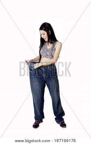 Diet concept. Young happy woman wearing her old jeans after success doing weight loss isolated on white background