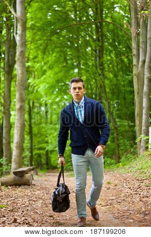 Picture Of A Young Fashion Man Strolling Outdoor With A Bag In His Hand