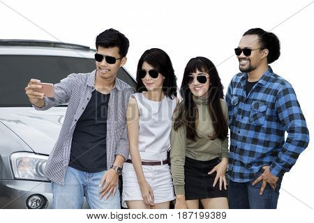 Multi ethnic of young friends taking selfie picture while standing in front of a car isolated on white background