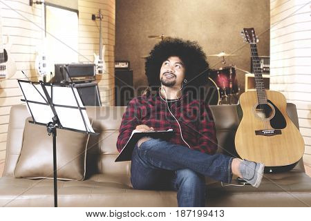 Young man composing a song while thinking idea by listening music on earphone in music studio