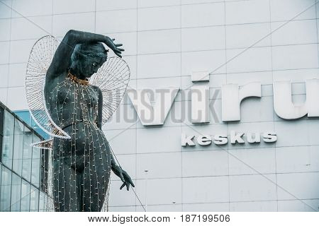 Tallinn, Estonia - December 2, 2016: Statue of a nude woman with her hand on her head and Viru trade center shopping mall on background.