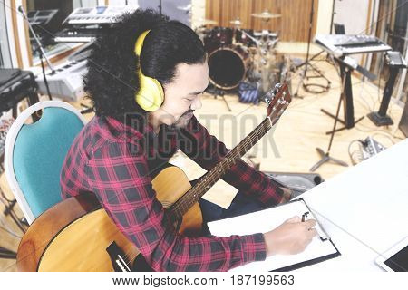 Young man wearing headphone composing a song and writing on clipboard while sitting in the music studio