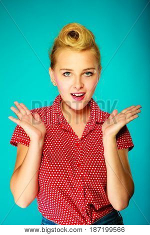 Shocking amazed astonished gestures concept. Shocked lovely pin up young girl holding head with hands. Studio shot on blue background