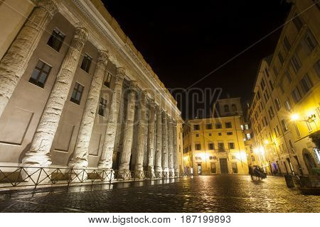 The Temple of Hadrian is a temple to the deified Hadrian on the Campus Martius in Rome, Italy. Roman columns. Bright moon in the dark sky.