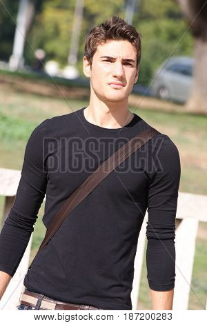 Fashionable and handsome young man outdoors. Wearing a casual clothes, black long sleeved t-shirt and jeans. Modern hairstyle. Behind him a park. Serious and confident look.