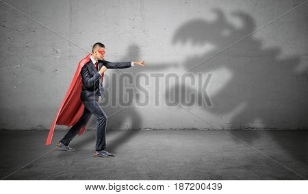 A superhero businessman fighting off a dragon shadow on concrete background. Business and success. Fighting off competition. Imaginary troubles.