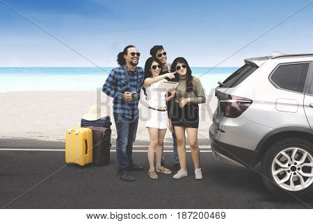 Multiracial group of young people standing near the beach while looking something with digital tablet