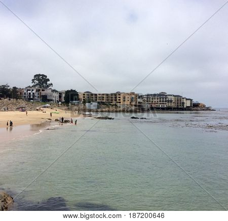 View of shoreline and the City of Pacific Grove  with the silhouettes of people on the beach in the distance and a cloudy day from a pier in Monterey California