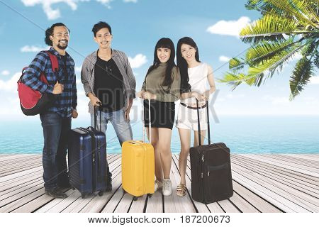 Multiracial of young people standing on seaside together while holding suitcase