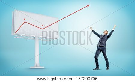 A happy businessman standing beside a large billboard with a red statistic arrow jumping out of it. Incredible profit. Unexpected income. Revenue report.