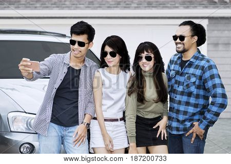 Multiracial young people taking selfie picture with smartphone while standing in front of the car on garage