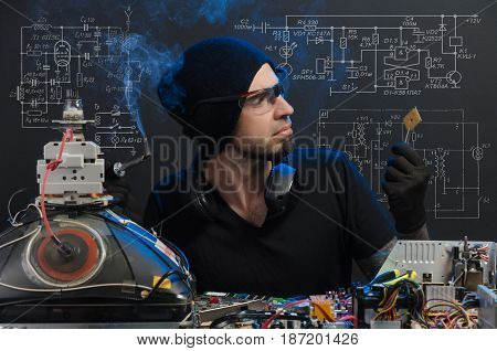 man is engaged in repair of electronics