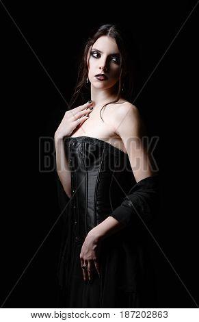 Dramatic portrait of a beautiful sad goth woman among the dark