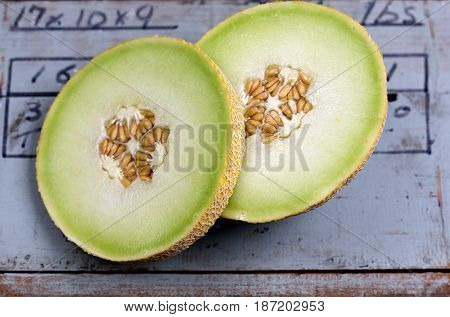 Detail of a ripe golden honeydew melon with its succulent velvety and sweet flesh on an antique farm timber box