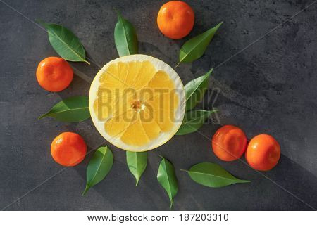 Half of pomelo and tangerines, on grunge background