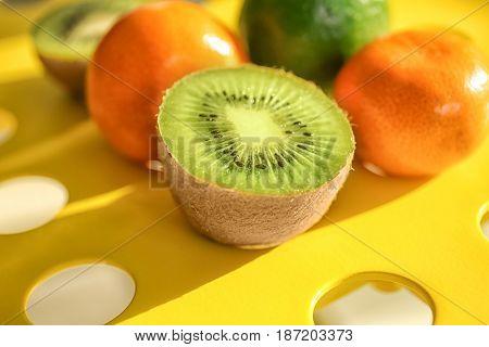 Juicy half of kiwi, fresh tangerines and lime on holey table