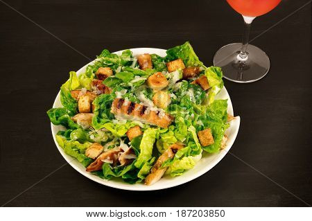 A photo of a plate of chicken Caesar salad, with a glass of rose wine, on a black background with a place for text