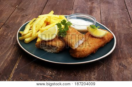 traditional British fish and chips on brown wooden background