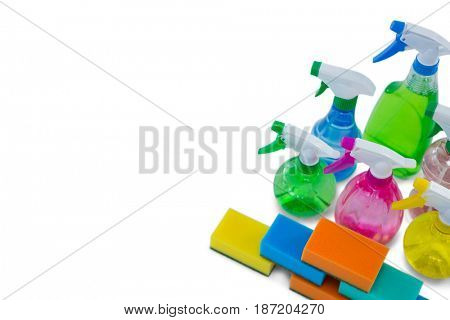 High angle view of spray bottles and cleaning sponge against white background