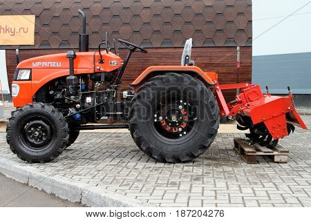 PERM RUSSIA-APRIL 21 2017: Red compact tractor with a hook-on device. Russia. Perm.