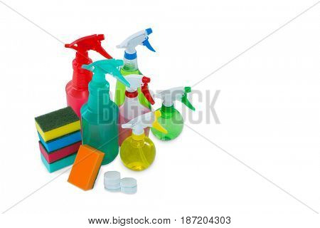 High angle view of colorful sponges and spray bottles against white background