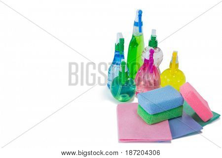 High angle view of colorful spray bottles with sponges and wipe pads against white background