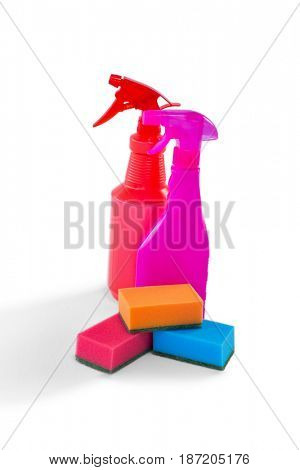 Colorful spray bottles and cleaning sponges against white background