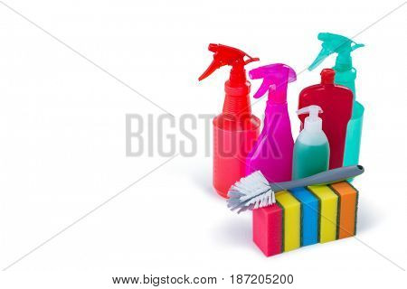 Cleaning sponges and brush with colorful spray bottles against white background