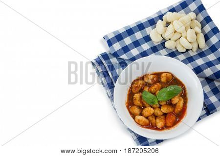 Overhead view of gnocchi pasta in bowl on napkin against white background