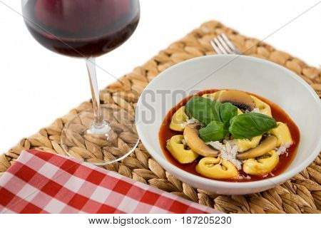 Close of cooked tortelloni in bowl on napkin by wineglass over white background