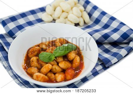 Close up of gnocchi pasta in bowl on napkin against white background