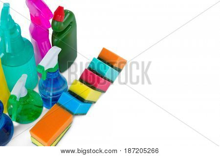 High angle view colorful sponges and spray bottles against white background