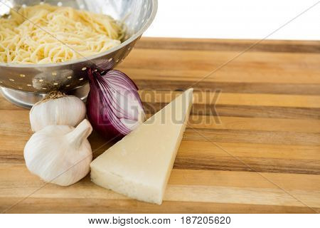 Close up of pasta in colander with ingredients on cutting board against white background