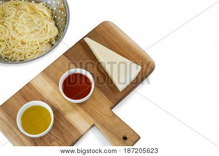 High angle view of pasta in colander by sauce and cheese on cutting board against white background