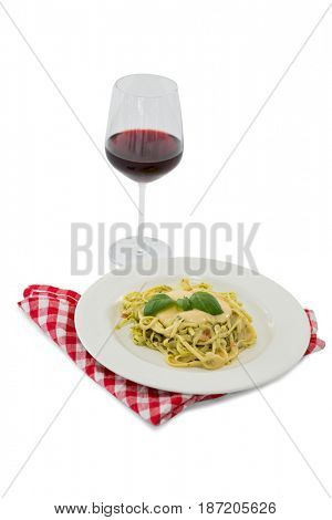 Pasta served in dish by wineglass against white background