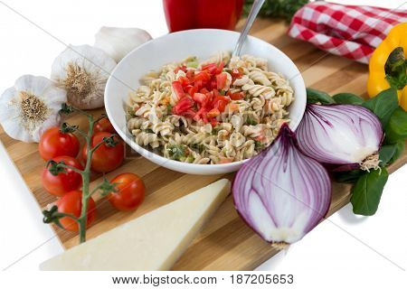 Pasta served in bowl amidst vegetables on cutting board against white background