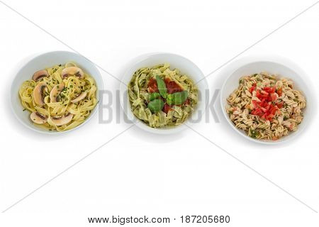 Overhead view of pastas served in containers against white background