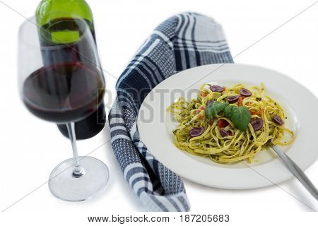 Close up of pasta served in plate by wine against white background