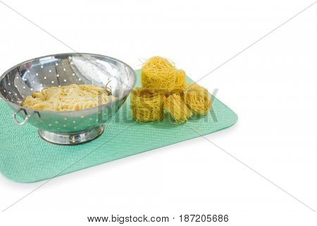 Close up of pasta in colander with tagliolini on place mat against white background