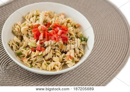 Close up of cooked rotini served in bowl on place mat over white background