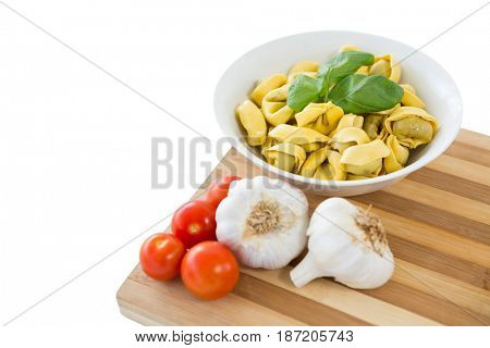 Close up of pasta served in bowl on cutting board against white background