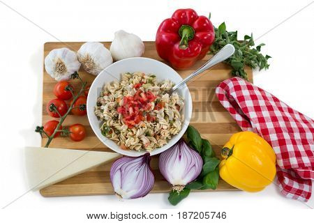 Overhead view of pasta served in bowl amidst vegetables on cutting board against white background