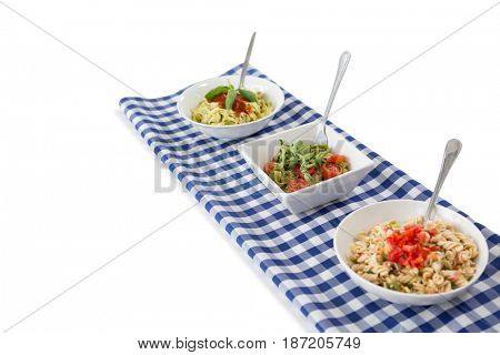 High angle view of pasta served in bowls on napkin against white background