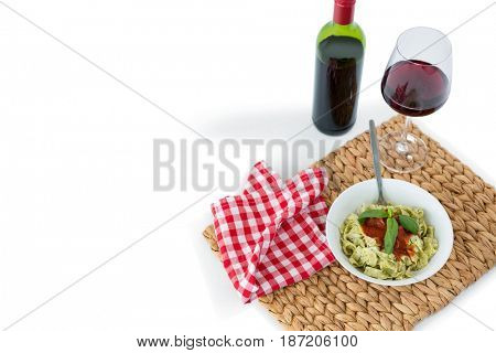 High angle view of oasta served in bowl on place mat with wine and napkin against white background