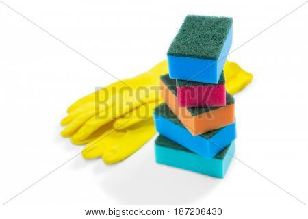 Close up of colorful sponges and gloves against white background