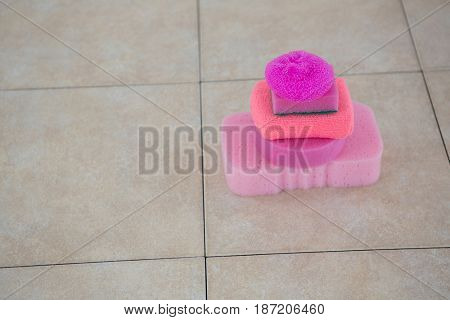 Close up of stacked sponges on tiled floor