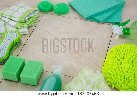 High angle view of green cleaning products arranged on tiled floor